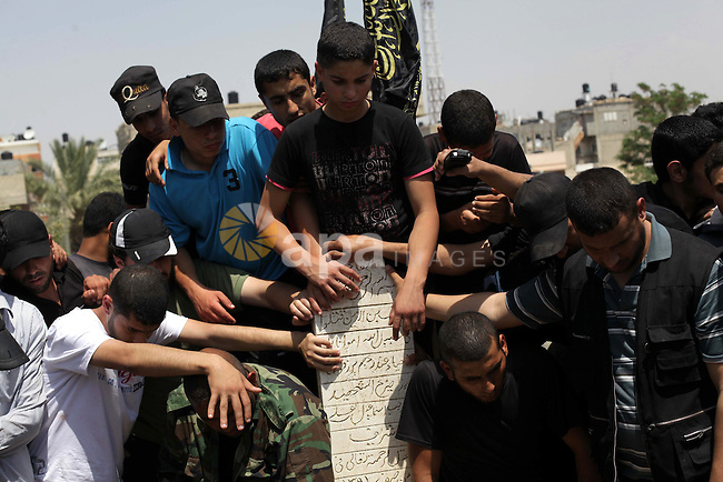 Palestinians gather around the grave of Haitham Al-Mes-hal, who relatives said belonged to a militant Jihadist Salafi organisation, after his burial at a cemetery in Gaza City April 30, 2013. Israel on Tuesday launched its first targeted attack on a militant in Gaza since a war in November, killing the Palestinian jihadist in an air strike that put further strain on a five-month-old ceasefire. Photo by Ashraf Amra