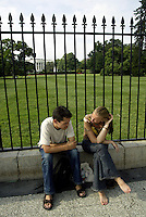 Jun 14, 2004; Washington DC, Washington, USA; Young man and woman tourists sit along the fence chatting about their visit to The White House behind them.