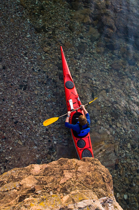 A male sea kayaker paddles a red kayak on Lake Superior at Presque Isle Park in Marquette Michigan.