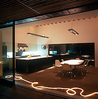 The kitchen/dining area has a dramatic lighting effect seen.here through the open sliding door to the terrace