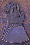 Pair of vintage brown leather gauntlets or large gloves lying on rusty metal sheet