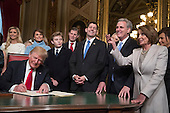 United States President Donald Trump is joined by the Congressional leadership and his family as he formally signs his cabinet nominations into law, in the President's Room of the Senate, at the Capitol in Washington, Friday, Jan. 20, 2017. From left behind Trump are, Ivanka Trump, Melania Trump, their son Barron Trump, Eric Trump, Speaker of the US House Paul Ryan (Republican of Wisconsin), US House Majority Leader Kevin McCarthy (Republican of California) and US House Minority Leader Nancy Pelosi (Democrat of California).<br /> Credit: J. Scott Applewhite / Pool via CNP