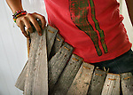 """Natalia Fernandez, 16, holds up a skirt made of the bark of a palm tree for her costume, called  """"El Danzante del Sonido,"""" the sound dancer in Spanish, as she makes her costume, at her home in Jayuya, Puerto Rico, on Tuesday, November 18, 2008. Fernandez was nominated by her school to parcipate in the Taino pageant in which girls are judged by their native look and design of their costume. Residents will celebrate the 39th annual Festival Indigena de Jayuya, which honors their Taino Indian heritage, this weekend."""
