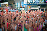 "Thousands of yoga practitioners pack Times Square in New York to practice yoga on the first day of summer, Monday, June 20, 2016. The 14th annual Solstice in Times Square, ""Mind Over Madness"",   stretches the yogis'  ability to block out the noise and the visual clutter that surround them in the Crossroads of the World. (© Richard B. Levine)"
