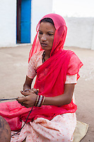 Suki (not her real name), churns milk in her house in Jhaju village, Bikaner, Rajasthan, India on 4th October 2012. Now 20, Suki was married off at age 12, but only went to live with her husband when she was 14. The three sisters, aged 10, 12, and 15 were married off on the same day by their maternal grandfather while their father was hospitalized. Her husband died three years after she moved in, leaving her with a daughter, now 6, and a son, now 4. She has no parents-in-laws and thus returned to her parents house after being widowed because her brother-in-law, who had become the head of the family after his brother's death, had refused to allow Suki to inherit her deceased husband's fair share of agriculture land. Although Suki's father wants her to remarry, she refuses to, hoping instead to be able to support her family through embroidery and tailoring work. The family also makes hand-loom cotton to subsidize their collective household income. Photo by Suzanne Lee for PLAN UK