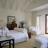 This bedroom has been decorated in shades of white, stone and black and has plantation shutters that lead on to a small balcony with a view of Johannesburg