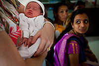 A European mother cradles her newborn in the Akanksha Infertility Clinic in the small town of Anand, Gujarat, India. The Akanksha Infertility Clinic is known internationally for its surrogacy program and currently has over a hundred surrogate mothers pregnant in their environmentally controlled surrogate houses.
