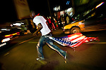 A Ghana supporter trails an American flag behind him as he races down Oxford Street in Accra, Ghana as Ghanaians took to the streets to celebrate their win over the USA on 26 June 2010 during the FIFA World Cup.