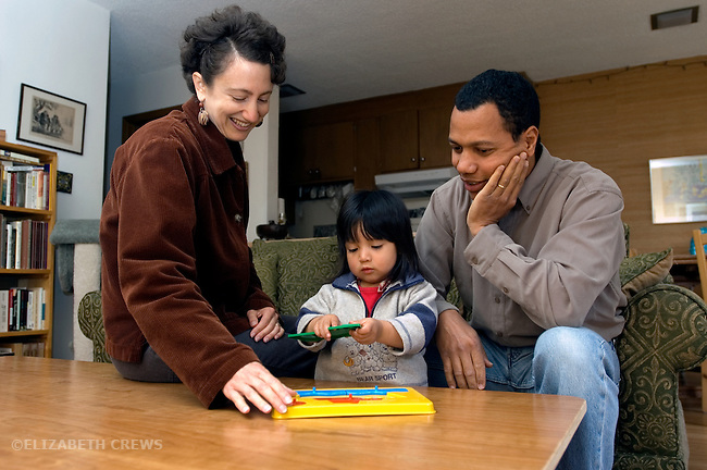 Berkelely CA Mixed race couple (Afro-cuban father) doing puzzle with adopted Guatemalan daughter, age two