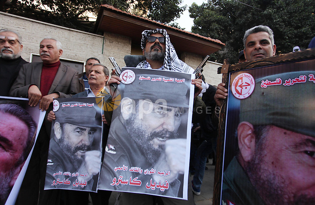 Palestinian men hold posters of late Cuban leader Fidel Castro during a gathering in Gaza city on November 28, 2016 to pay tribute him after his death. Cuban revolutionary icon Fidel Castro died late November 25 in Havana, his brother, President Raul Castro, announced on national television. Castro's ashes will be buried in the historic southeastern city of Santiago on December 4 after a four-day procession through the country. Photo by Ashraf Amra