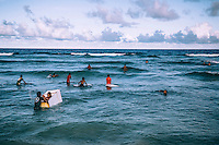 Teenagers trying to 'catch a wave', 'surfing' with any available floating materials.