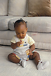 Richmond, CA  African American baby girl twelve months old showing ability to grasp a block in each hand at play at home  MR