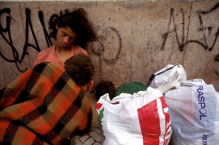 A young mother naps on a busy sidewalk with two sons in downtown Rio de Janeiro. Homelessness is a giant problem in the city of 12 million, where the rural poor flock in search of jobs.