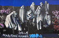 Section of the Berlin Wall depicting an untitled painting of shrouded figures by Ana Leonor Madeira Rodrigues, damaged by graffiti, part of the East Side Gallery, a 1.3km long section of the Wall on Muhlenstrasse painted in 1990 on its Eastern side by 105 artists from around the world, Berlin, Germany. Picture by Manuel Cohen