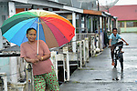 A woman stands under an umbrella in Kuala Bubon, in Indonesia's Aceh province. The community of 118 houses was built by the ACT Alliance after the village's tsunami survivors refused to accept government plans to relocate them inland far from the sea. After the houses were built, the community then successfully fought a government plan to demolish part of the new village to make way for a new highway.