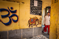 A Hindu priest leaves a temple that is adorned with the Hindi script for OM said to be &quot;the sound of the universe.&quot;