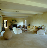 Contemporary furniture in loose covers is grouped around a low rustic table in this spacious low-ceilinged living room