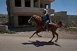 A man takes a kid for a ride on his horse during Syria's independence day, in the Druze village of Majdal Shams, Golan Heights.