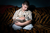 Portrait of Russian army hazing victim Andrei Sychyov with his cat at home in Yekaterinburg..On New Yearís Day in 2006 in the barracks of the Chelyabinsk Tank Academy, a sergeant, possibly drunk, meted out punishment to Pvt. Andrei S. Sychyov..Private Sychyov was forced to squat for three and a half hours. When he complained, as the pain worsened, the sergeant stomped on his ankle twice..Private Sychyov suffered injuries that resulted in infection, then in the amputation of his both legs, a finger, and genitals. .His case became the biggest scandal to reflect the state of Russia's army and the country's human rights situation.