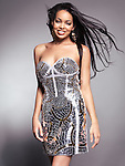 Smiling young black woman with long flying hair wearing fancy shiny dress isolated on gray background