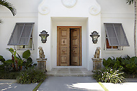 The large wooden doors of the Spanish-style entrance are guarded by a pair of carved hounds situated under large metal lanterns