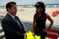 City attorney Michael Aguirre speaks to Marcelle Teran of the safebeaches.org group before Council Member Kevin Faulconer and Council President Scott Peters held a joint press conference in Mission Beach Tuesday, July 22rd 2008 to announce that they will bring a proposal to put the ban on the November Ballot before the council at the next meeting.  Residents, business owners and media attended the rally with the overwhelming majority apparently in favor of the alcohol ban.