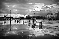 A cyclist rides after a storm rain on Place des Invalides, Paris
