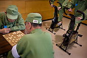 Elderly prisoners playing Japanese board game 'shogi',  during recreational time in an indoor recreational room, whilst two fellow inmates use the exercise bikes, in Onomichi prison, Japan.  Monday, May 19th 2008
