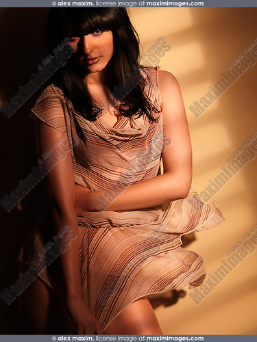 Beautiful young woman in light flying dress standing in light coming through a window. Artistic dynamic fashion photo.
