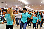 "Flash Mob dance at Macy's for Estee Lauder,  in Roosevelt Field, Garden City, New York, USA, on July 23, 2011. Teal shirts dancers wearing have ""Imagine having nothing to hide"" written on front.  NOTE: Motion blur, focus on ""imagine having nothing to hide"" on shirt of center dancer; taken of dancers in available light in store"