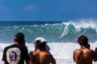 Tourists and photographers watch the big wave surfing scene at Waimea Bay, North Shore, O'ahu.