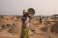 Togo - Lomé - A local woman sand mining on the beach. Aside from climate change, other man-made activities such as sand mining, mangroves harvesting, river dams and the construction of deep-sea ports have increased coastal erosion by either preventing sediments from reaching the coasts of by disrupting their natural movements.
