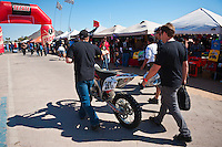 Team 201x walks motorcycle along Malecon to Tech inspection, 2012 San Felipe Baja 250, Baja California, Mexico