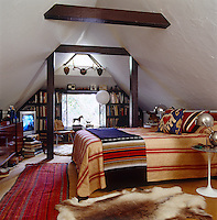 Striped fabric covers the bed in this attic bedroom which has a custom made bookshelf built around the window