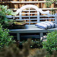 A blue painted garden bench against a rough wooden fence