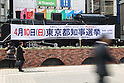 March 24, 2011, Tokyo, Japan - A man walks past a banner for the Tokyo gubernatorial elections hang on at Shimbashi district on Thursday, March 24, 2011. The natiowide local elections campaign officially kick off today in 12 prefectures ahead of voting on April 10, while Iwate Prefecture has put off its race in the aftermath of the March 11 catastrophic earthquake. (Photo by YUTAKA/AFLO) [1040] -ty-