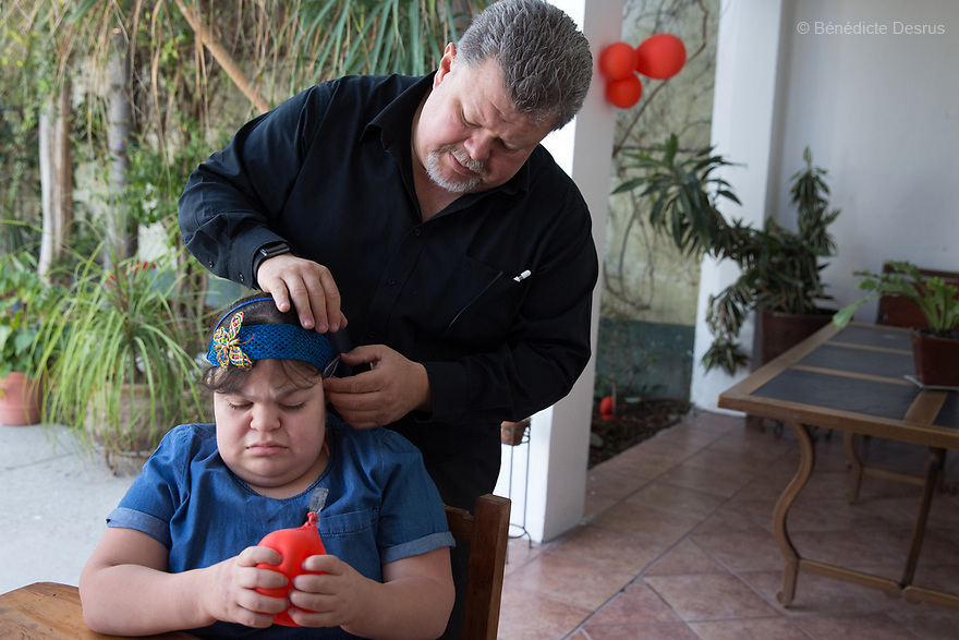 "Ana Ximena Navarro and her father Jesús Navarro Torres, at their home in Guadalajara, Mexico on February 22, 2017. Ximena was diagnosed as an infant with Hurler syndrome. Hurler syndrome is the most severe form of mucopolysaccharidosis type 1 (MPS1), a rare lysosomal storage disease, characterized by skeletal abnormalities, cognitive impairment, heart disease, respiratory problems, enlarged liver and spleen, characteristic facies and reduced life expectancy. Ximena was being given enzyme replacement therapy (ERT) when she was 19 months old, and she was suddenly able to eat and sleep. She is now 12, and has normal hormonal development for her age, although some mental delay, according to her father. ""Without the treatment, she would have died from all the complications — untreated, children have a very bad quality of life and typically die before they are seven"", her father says. Photo credit: Bénédicte Desrus"