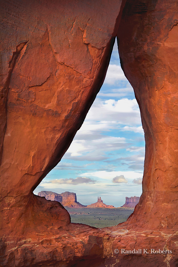 Teardrop arch frames a view of Monument Valley on the Utah-Arizona border.