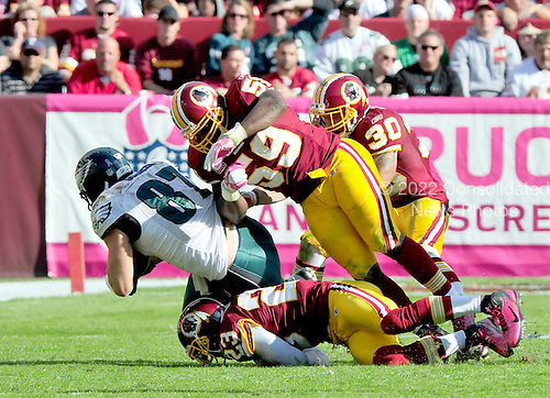 Philadelphia Eagles tight end Brent Celek (87) makes a reception and is tackled by Washington Redskins cornerback DeAngelo Hall (23), linebacker London Fletcher (59), and safety LaRon Landry in late third quarter action at FedEx Field in Landover, Maryland on Sunday, October 16, 2011.  The Eagles won the game 20 - 13..Credit: Ron Sachs / CNP