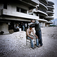 Mustafa cuts Asife's hair outside an abandoned building where they squat. Patras is home to about 3,000 illegal immigrants. Most of them are Afghans, although there are also some Iranians and Uzbeks. They stop in Patras to try and find passage to various European destinations by hiding in ships, containers and trucks parked in the port. If they are lucky they will make it to their destination. Many of them live in shacks made from cartons, plastic and wood they found on the beach. To shelter from the cold they also squat in abandoned buildings, living without water and electricity. The living conditions are inhumane and unhygienic.