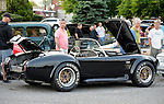 Bellmore, New York, USA. May 29, 2015. Visitors look at an original Black 1965 Shelby Cobra 427 roadster racing car, with open hood and trunk, displayed at the Friday Night Car Show held at the Bellmore Long Island Railroad Station Parking Lot. Hundreds of classic, antique, and custom cars are generally on view at the free weekly show, sponsored by the Chamber of Commerce of the Bellmores, from May to early October.
