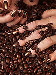 Closeup of woman's hands with brown nail polish in coffee beans