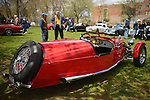 Floral Park, New York, U.S. - April 27, 2014 - Owner STEVE KAPLAN (in brown vest) discusses his red BRA CX3, a custom Beribo Replica Automobiles kit vehicle with three wheels, and registered by DMV as a 2009 Custom Motorcycle, with a visitor at the 35th Annual Antique Auto Show at Queens Farm. A wire spare tire is attached to the outside of the rear of the unusual vehicle.