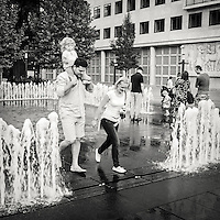 Family walking though a motion controled fountain in central Budapest Hungary