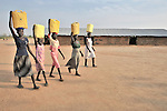 Girls in Yei, Southern Sudan, walk home after getting water from a well provided by the United Methodist Committee on Relief (UMCOR).