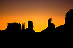Sunset silhouetting the desert landscape and rock formations of Monument Valley. <br />