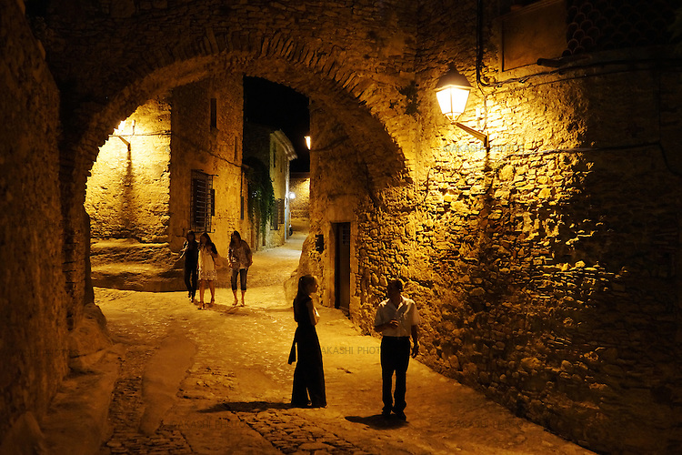 Tourists walk at night the medieval village of Peratallada.
