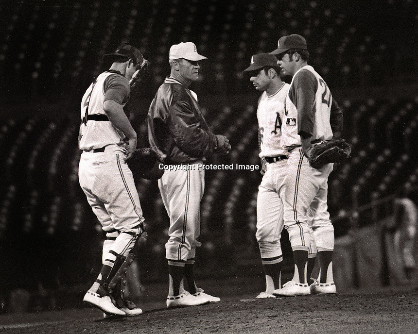 "Athletics1968: Manager Hank Bauer visits the mound with catcher Phil Rook, Sal Bando and pitcher Jim ""Catfish"" Hunter. (1968 photo by Ron Riesterer)"