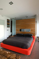 In the master bedroom a ceiling height partition separates the sleeping area from the bathroom and also doubles as a headboard with useful built-in storage