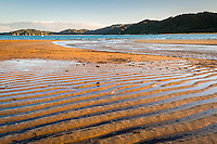 Sun sets on golden beach in Totaranui, Abel Tasman National Park, Nelson Region, New Zealand